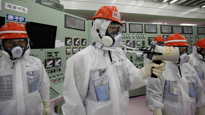 An employee (C) of Tokyo Electric Power Co. (TEPCO) measures using a dosimeter at the central operating control room of the No. 1 and No. 2 reactors at TEPCO's tsunami-crippled Fukushima Daiichi nuclear power plant at Fukushima prefecture (Reuters/Koji Sasahara)