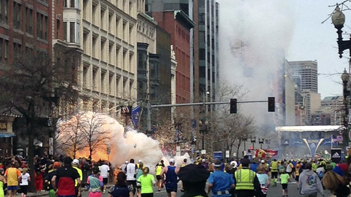 Runners continue to run towards the finish line of the Boston Marathon as an explosion erupts near the finish line of the race in this photo exclusively licensed to Reuters by photographer Dan Lampariello after he took the photo in Boston, Massachusetts, April 15, 2013. (Reuters/Dan Lampariello)