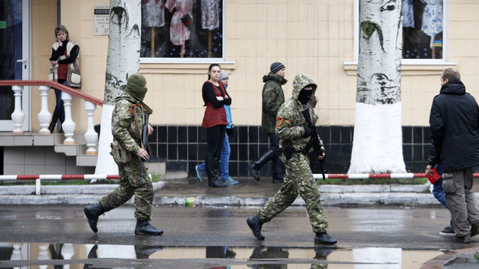 People watch arned men near a regional police building seized by armed separatists in Slavyansk on April 13, 2014 (AFP Photo / Anatoly Stepanov)