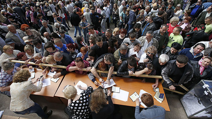 People stand in a line to receive ballots from members (front) of a local election commission during the referendum on the status of Donetsk region in the eastern Ukrainian city of Mariupol May 11, 2014. (Reuters / Marko Djurica)
