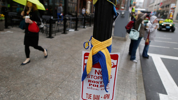 A pedestrian walks past a scarf and a traffic sign near the site of one of the two bomb blasts on the one-year anniversary of the 2013 Boston Marathon bombings in Boston, Massachusetts, April 15, 2014. (Reuters / Dominick Reuter)