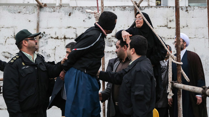 The mother (R) of Abdolah Hosseinzadeh, who was murdered in 2007, slaps Balal who killed her son during the execution ceremony in the northern city of Nowshahr on April 15, 2014 just before she removed the noose around his neck with the help of her husband, sparing the life of her son's convicted murderer. (AFP Photo / Arash Khamooshi / ISNA)
