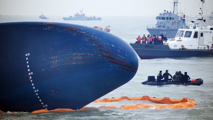 Coast guard members search for passengers near a South Korean ferry (C) that capsized on its way to Jeju island from Incheon, at sea some 20 kilometres off the island of Byungpoong in Jindo on April 17, 2014. (AFP Photo / Ed Jones)