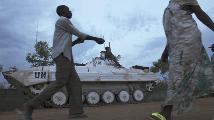Displaced people walk past a U.N. armoured vehicle inside the United Nations Mission in South Sudan (UNMISS) camp in Malakal, Upper Nile State, March 3, 2014.  (Reuters/Andreea Campeanu)