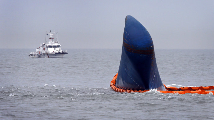 "A vessel involved in search and rescue operations passes near the upturned South Korean ferry ""Sewol"" in the sea off Jindo April 17, 2014. (Reuters/Kim Kyung-Hoon)"