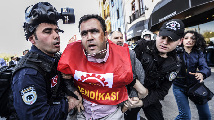 Turkish riot policemen detain a unionist in Taksim Square in Istanbul on April 21, 2014 as security forces prevent union members from issuing a press statement regarding a May Day celebration. (AFP Photo/Bulent Kilic)