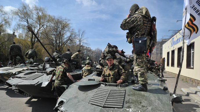 Armed men wearing military fatigues gather by Armoured Personnel Carriers (APC) as they stand guard outside the regional state building in the eastern Ukrainian city of Slavyansk on April 16, 2014 (AFP Photo / Genya Savilov)