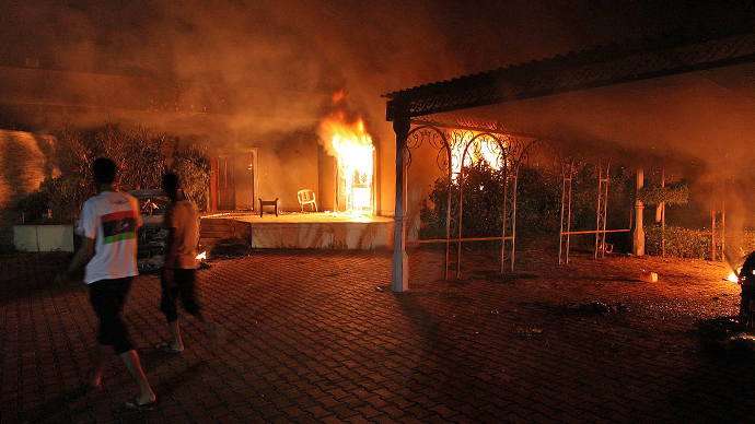 A vehicle (R) and the surrounding buildings burn after they were set on fire inside the US consulate compound in Benghazi late on September 11, 2012. (AFP Photo)