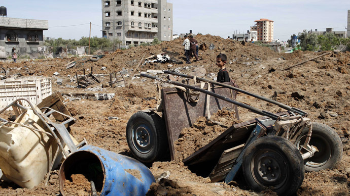A Palestinian boy looks at the scene of an Israeli air strike in the central Gaza Strip April 21, 2014. (Reuters/Ibraheem Abu Mustafa)