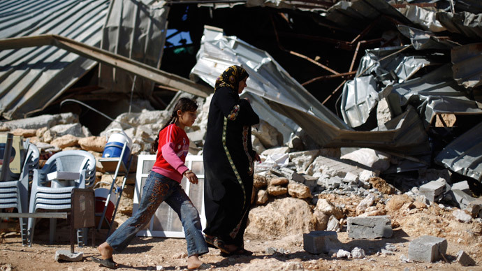 Palestinians walk past a structure after it was demolished by Israeli bulldozers in Khirbet Al-Taweel village near the West Bank City of Nablus April 29, 2014. (Reuters / Mohamad Torokman)