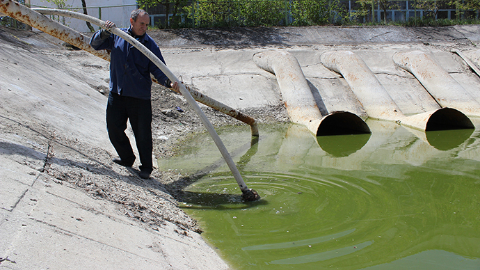 A picture taken in the Crimea's Kirovsky region on April 27, 2014, shows a man pomping out water from the nearly empty Northern Crimean Canal, which supplies the peninsula's water. (AFP Photo / Yuriy Lashov)