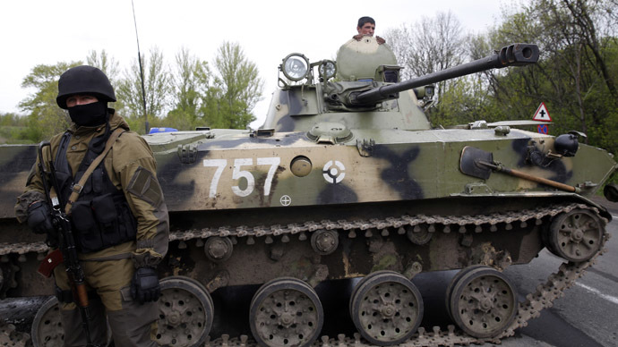 A Ukrainian soldier stands guard in front of an armoured personnel carrier on a road at a check point near the village of Malinivka, southeast of Slaviansk, in eastern Ukraine April 29, 2014. (Reuters/Baz Ratner)