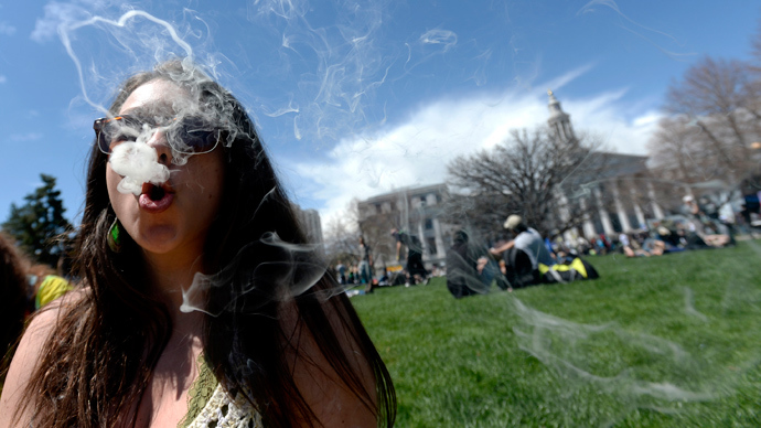A woman blows smoke rings with marijuana smoke during the 4/20 Rally at the Civic Center in Denver, Colorado, April 20, 2014 (Reuters / Mark Leffingwell)