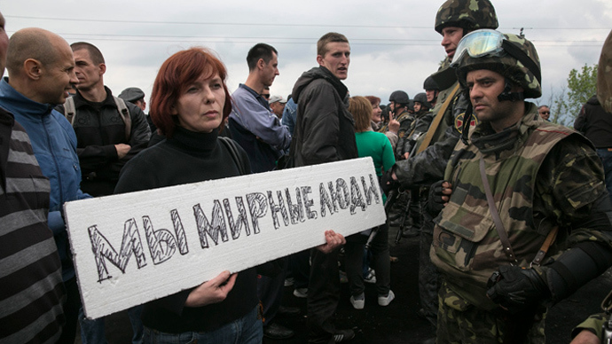 "A civilian holds a sign reading ""We are peaceful people"" in front of Ukrainian troops at a checkpoint near Slavyansk on May 2, 2014 (Reuters / Baz Ratner)"