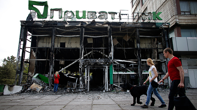 People walk past a gutted branch of Privat Bank near the town hall in Mariupol, eastern Ukraine May 4, 2014 (Reuters / Marko Djurica)