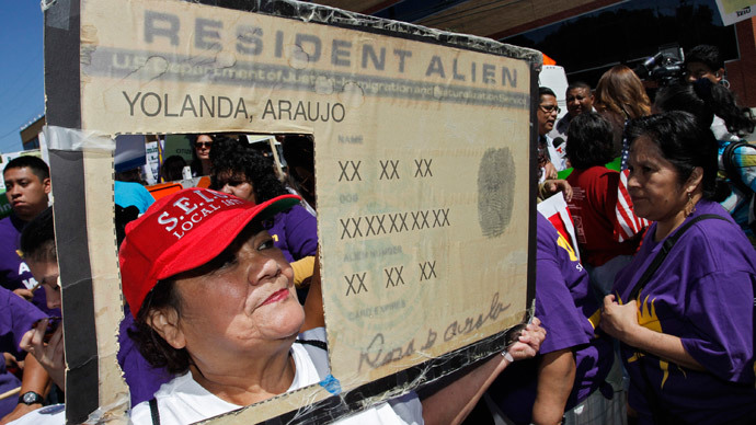 Protester Yolanda Araujo holds a mock resident alien card at a rally for immigration reform near Senator Dianne Feinstein's office, in Los Angeles, California (Reuters / Jonathan Alcorn)
