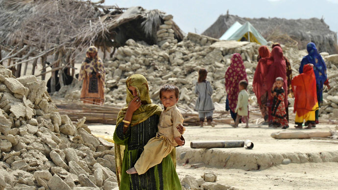 Pakistani earthquake survivors walk next to their destroyed houses in Peerander on September 29, 2013. (AFP Photo/Banaran Khan)