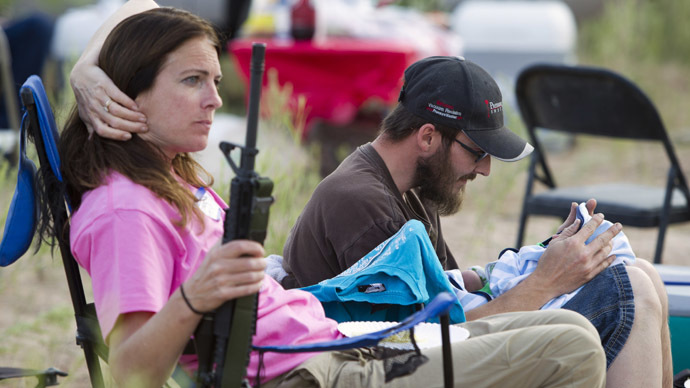 "Chris Shelton of Las Vegas interacts with his 1-week-old son as his mother Shelley Shelton holds his rifle during a Bundy family ""Patriot Party"" near Bunkerville, Nevada, April 18, 2014. (Reuters/Steve Marcus)"