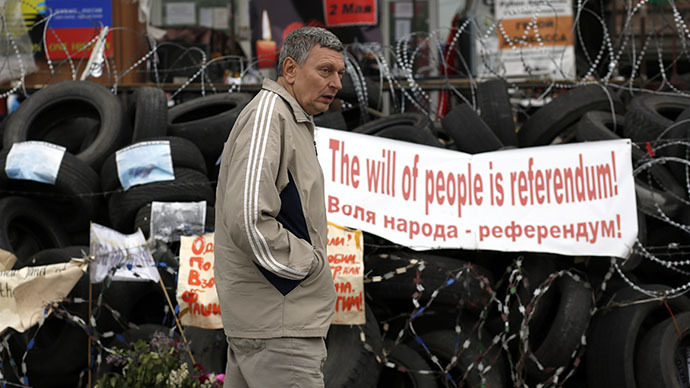 A man walks past a barricade outside a regional government building in Donetsk, eastern Ukraine May 8, 2014. (Reuters / Marko Djurica)