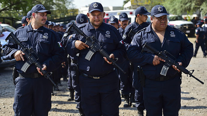 Members of the local Self-Protection Police wearing the uniforms of the new rural police, parade in Tepalcatepec, Michoacan State, Mexico, on May 10, 2014. (AFP Photo / Ronaldo Schemidt)