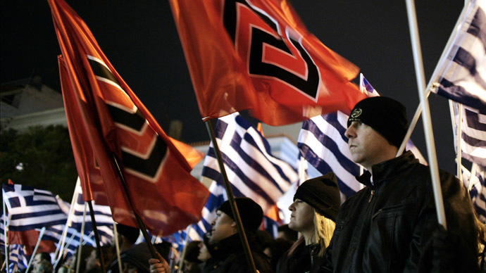 Member of the far right Golden Dawn party hold flags as they take part in a rally in Athens on February 1, 2014. (AFP Photo/Louisa Gouliamaki)