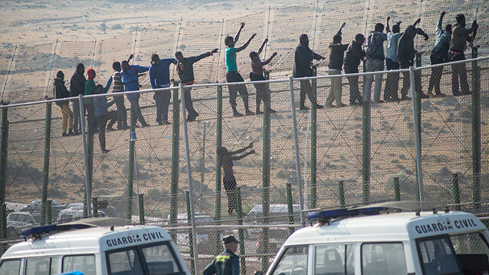 Would-be immigrants stand atop a boarder fence separating Morocco from the north African Spanish enclave of Melilla on May 1, 2014, following a morning assault on the boarder in an attempt to cross into Spain (AFP Photo)