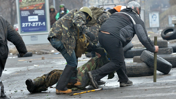 Anti-government protestors evacuate a comrade wouned by a sniper during clashes with the police in the center of Kiev on February 20, 2014. (AFP Photo/Sergei Supinsky)