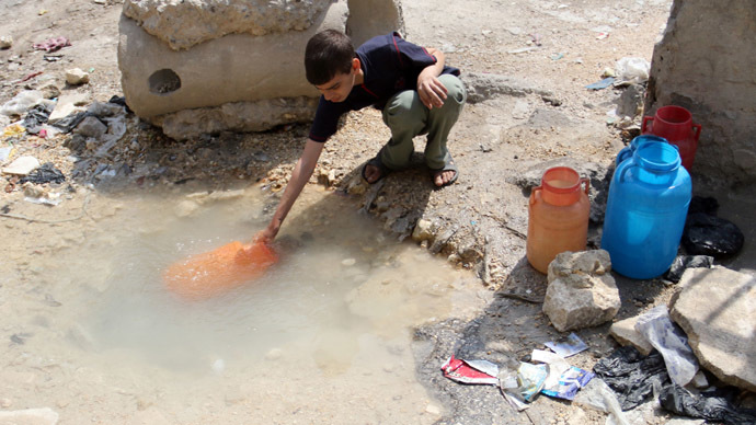 A boy collects water from the side of a road in a rebel-held area in Aleppo on May 12, 2014.  (AFP Photo/Zein Al-Rifai)