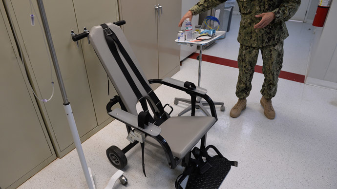 "This photo reviewed by the US military and made during an escorted visit shows a US naval medic explaining the ""feeding chair"" procedures at the detention facility in Guantanamo Bay, Cuba.(AFP Photo / Mladen Antonov)"