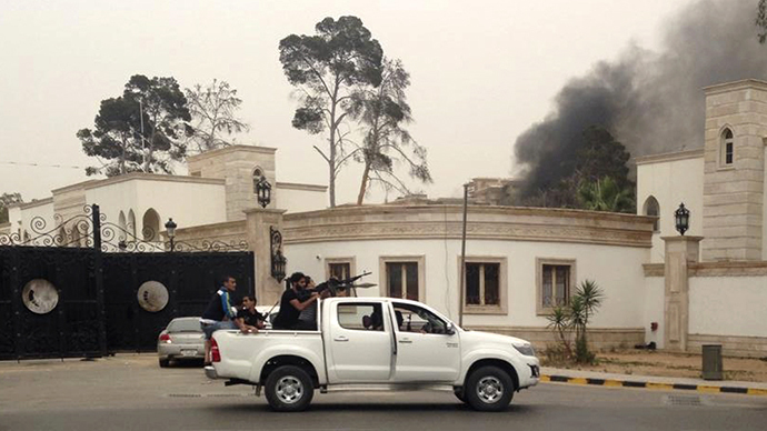Armed men aim their weapons from a vehicle as smoke rises in the background near the General National Congress in Tripoli May 18, 2014. (Reuters)