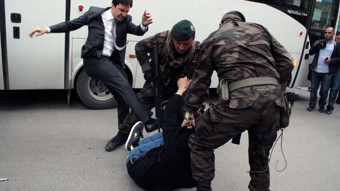 Photo taken on May 14, 2014shows a person identified by Turkish media as Yusuf Yerkel, advisor to Turkish Prime Minister Recep Tayyip Erdogan, kicking a protester already held by special forces police members during Erdogan's visit to Soma, Turkey.(AFP Photo / Depo Photos )
