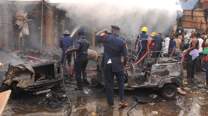 Firefighters extinguish a fire at the scene of a bomb blast at Terminus market in the central city of Jos on May 20, 2014 (AFP Photo / STR)