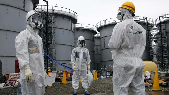 Tokyo Electric Power Corp's (TEPCO) official (C) and journalists wearing protective suits and masks stand in front of storage tanks for radioactive water in the H4 area, where radioactive water leaked from a storage tank in August, at the tsunami-crippled TEPCO Fukushima Daiichi nuclear power plant in Fukushima prefecture November 7, 2013. (Reuters/Kimimasa Mayama)