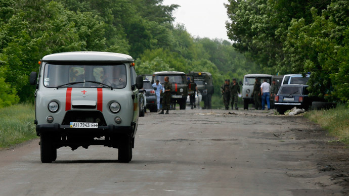 An ambulance carrying dead Ukrainian soldiers travels off the site (seen in background) killed on the outskirts of the eastern Ukrainian town of Volnovakha, south of Donetsk, May 22, 2014.(Reuters / Yannis Behrakis )