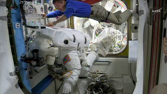 This April 23, 2014 NASA TV image shows International Space Station(ISS) astronaut Koichi Wakata(Top) of Japan assisting fellow astronaut Steve Swanson(L) (AFP Photo)