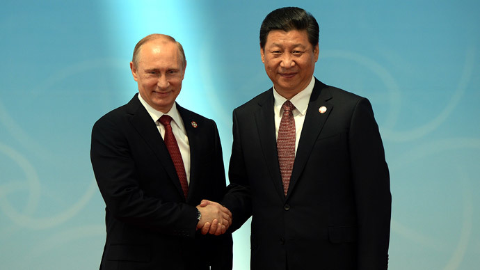 Russian President Vladimir Putin (L) is greeted by Chinese President Xi Jinping.(AFP Photo / Mark Ralston )