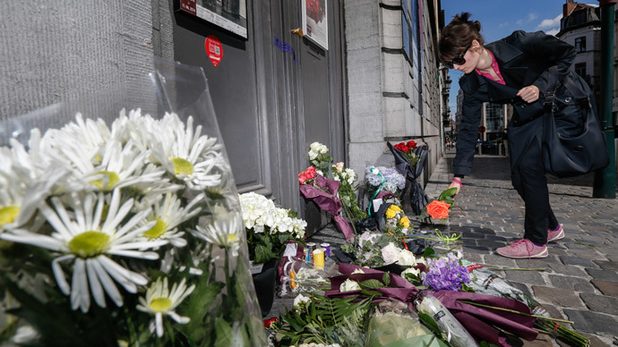 A woman lays a flower on the pavement in front of the Jewish Museum of Brussels on May 25, 2014 where an attack by a probable lone gunman the day before killed two Israelis and a French woman.  (AFP Photo / Belga / Thierry Roge)