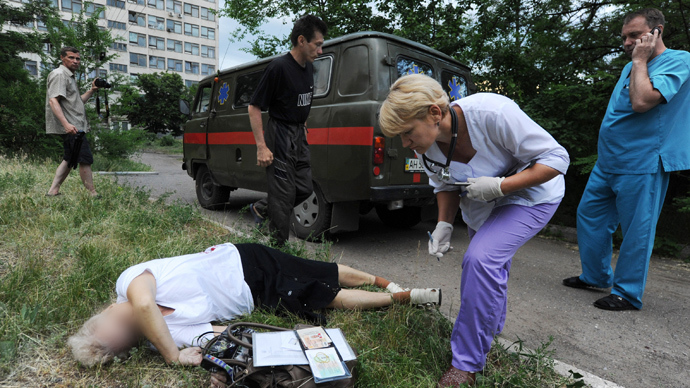 A doctor looks at documents as she examines the body of a woman killed as a result of fighting in the eastern Ukrainian city of Slavyansk on May 26, 2014 (AFP Photo / Viktor Drachev)