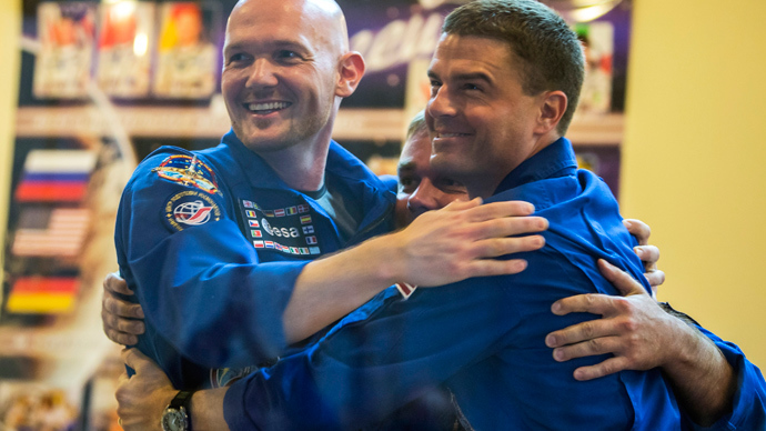 International Space Station crew members (L-R) Alexander Gerst of Germany, Maxim Surayev of Russia and Reid Wiseman of the U.S. hug one another at a news conference behind a glass wall at Baikonur cosmodrome May 27, 2014 (Reuters / Shamil Zhumatov)