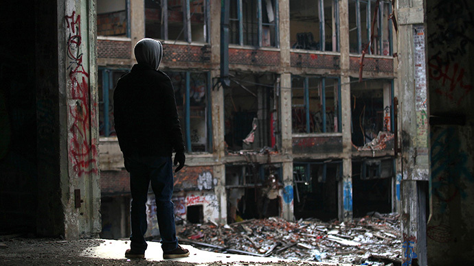 A man looks at the exterior of the abandoned Packard Automotive Plant December 13, 2013 in Detroit, Michigan. (AFP Photo / Getty Images / Joshua Lott)