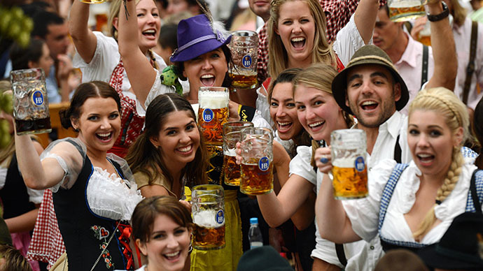 Visitors wearing traditional Bavarian clothes raise their  beers in a festival tent at the start of the Oktoberfest beer festival at the Theresienwiese in Munich, southern Germany. (AFP Photo / Christof Stache)