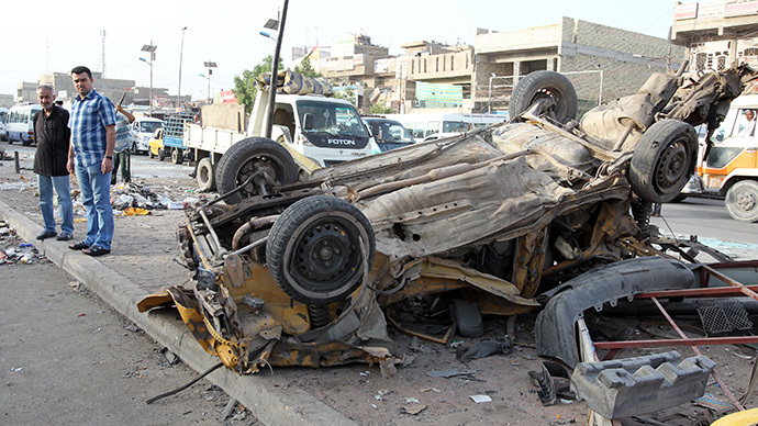 Iraqis inspect destruction in the street following an explosion the previous day in Sadr City, Baghdad's northern Shiite-majority district, on May 29, 2014. (AFP Photo / ALI Al-Saadi)