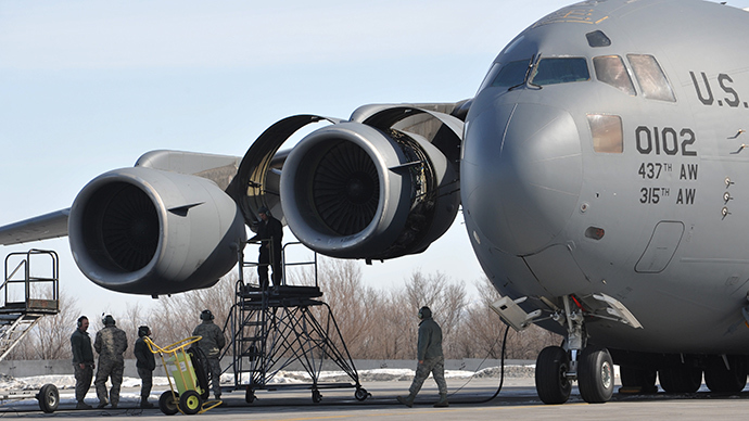 US servicemen perform their daily routines by a 437th Air Wing C-17 military transport plane on the runway at the US transit center in Manas, 30 kilometers outside Kyrgyzstan's capital Bishkek on March 6, 2014 (AFP Photo / Vyacheslav Oseledko)