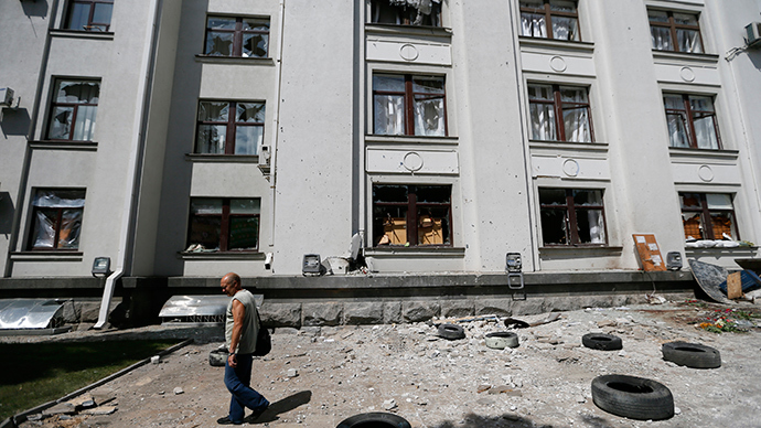 A man walks past the site of an explosion in a regional administration building in the eastern Ukrainian city of Luhansk June 3, 2014 (Reuters / Gleb Garanich)
