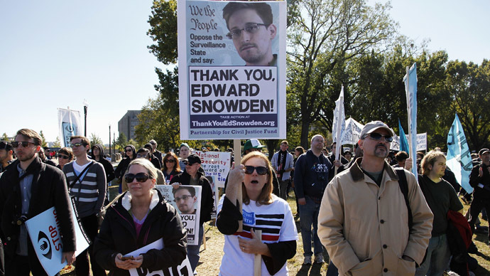"Demonstrators hold signs supporting fugitive former NSA contractor Edward Snowden as they gather for the ""Stop Watching Us: A Rally Against Mass Surveillance"" near the U.S. Capitol in Washington, October 26, 2013. (Reuters/Jonathan Ernst)"
