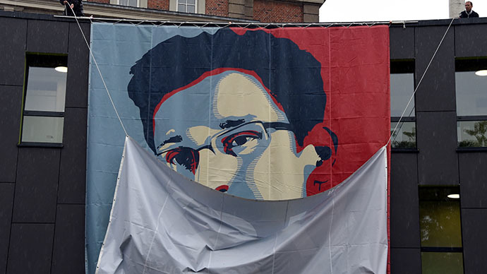 Students of the Muthesius Academy of Fine Arts and Design in Kiel uncoil a placard showing US intelligence leaker Edward Snowden as part of a campaign by German activists to grant asylum for Snowden. (AFP Photo / Carsten Rehder)