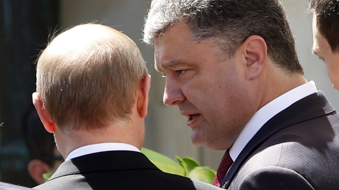Ukraine president-elect Petro Poroshenko (R) talks to Russian President Vladimir Putin after a group photo during the 70th anniversary of the D-Day landings in Benouville, France June 6, 2014. (Reuters/Kevin Lamarque)