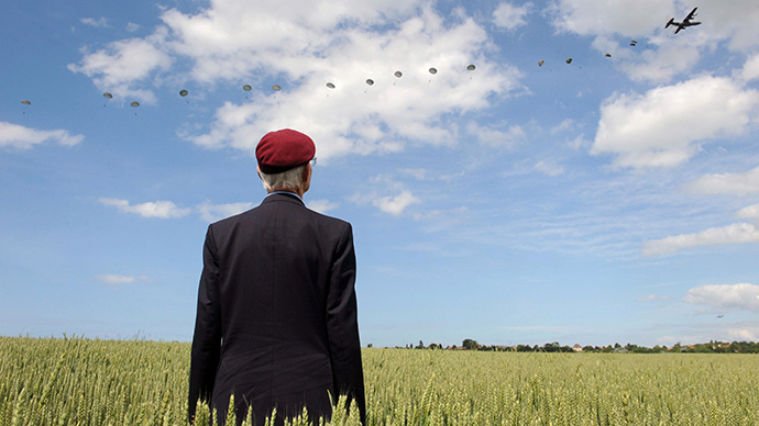 British WWII veteran Frederick Glover poses for a photograph as soldiers parachute down during a D-Day commemoration event on June 5, 2014. (AFP Photo / Thomas Bregardis)