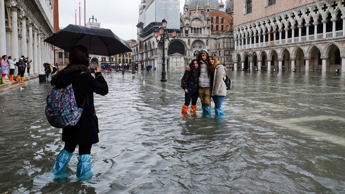 Tourists pose for a photo in a flooded St. Mark's Square during a period of seasonal high water in Venice (Reuters / Manuel Silvestri)
