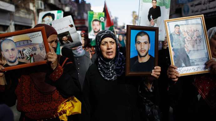 Palestinians hold pictures of prisoners during a demonstration in support of Palestinian prisoners on hunger strike in Israeli jails, in the West Bank city of Ramallah June 7, 2014.(Reuters / Mohamad Torokman)